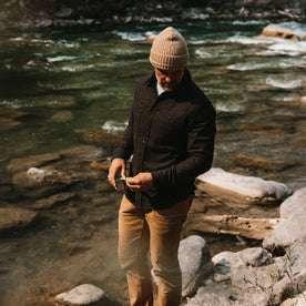 fit model wearing The Service Shirt in Moss Melange Wool, looking down in creek