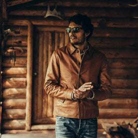 fit model wearing The Cuyama Jacket in Cognac, hands clasped by cabin