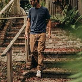 our fit model wearing The Après Pant in British Khaki Seersucker—walking down stairs