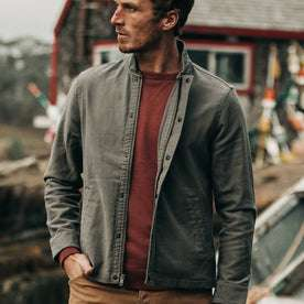 fit model wearing The Bomber Jacket in Charcoal Jungle Cloth, hand in pocket, looking left of camera