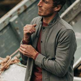 fit model wearing The Bomber Jacket in Charcoal Jungle Cloth, playing with sleeve near boat