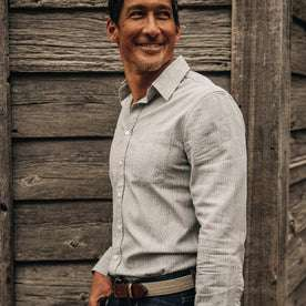 fit model wearing The California in Midnight Slub Micro Stripe, next to wood wall, smiling side profile shot