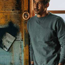 fit model wearing The Crewneck in Sea Green Terry, in boathouse, leaning against window
