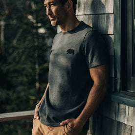 fit model wearingThe Embroidered Heavy Bag Tee in Grey Bear, leaning against house