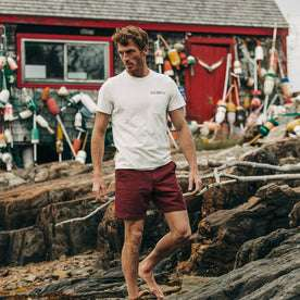 fit model wearing The Heavy Bag Tee in Atlantic, standing on rocks
