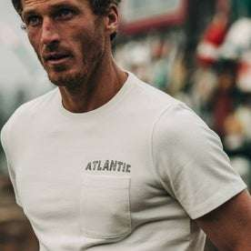 fit model wearing The Heavy Bag Tee in Atlantic, cropped shot of chest near water