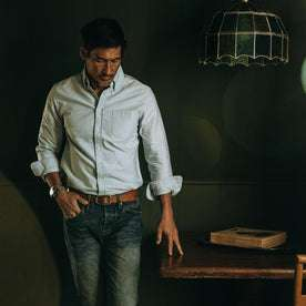 fit model wearing The Jack in Blue Everyday Oxford, next to table, inside