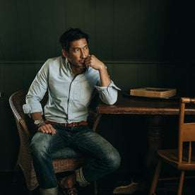 fit model wearing The Jack in Blue Everyday Oxford, sitting, looking right