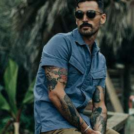fit model wearing The Jungle Shirt in Ocean, sitting, looking left of screen