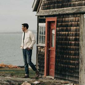 fit model wearing The Long Haul Jacket in Natural Organic Selvage, standing near red door