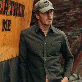 fit model wearing  The Mechanic Shirt in Dark Olive Herringbone, hat on—leaning against boat