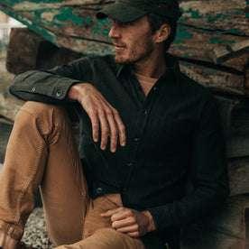 fit model wearing  The Mechanic Shirt in Dark Olive Herringbone, hat on—sitting near boat