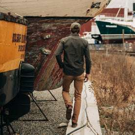 fit model wearing  The Mechanic Shirt in Dark Olive Herringbone, hat on—walking away from camera
