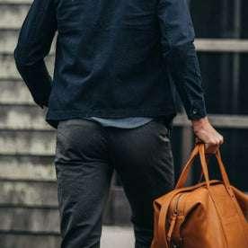 fit model wearing The Morse Pant in Charcoal Slub Linen, back shot holding bag
