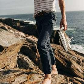 fit model wearing The Morse Pant in Navy Slub Linen, walking on rocks