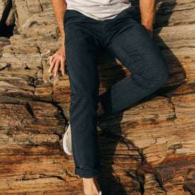 fit model wearing The Morse Pant in Navy Slub Linen, sitting on rocks