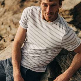 fit model wearing The Organic Cotton Tee in Graphite Stripe, cropped shot, sitting on rocks