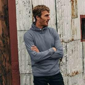 fit model wearing The Shackleton Hoodie in Ocean, arms crossed, looking right