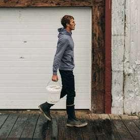 fit model wearing The Shackleton Hoodie in Ocean, walking with bucket