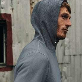 fit model wearing The Shackleton Hoodie in Ocean, hoodie up, cropped shot
