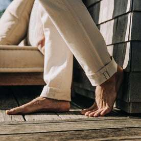 fit model wearing The Slim Jean in Natural Organic Selvage, cuffed, barefoot on deck