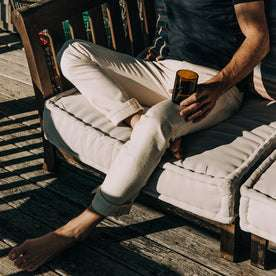 fit model wearing The Slim Jean in Natural Organic Selvage, sitting, holding glass