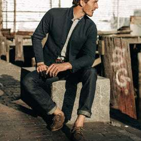 fit model wearing The Slim Jean in Organic Selvage, sitting near dock