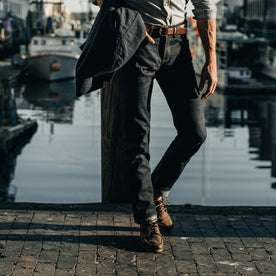 fit model wearing The Slim Jean in Organic Selvage, cuffed with shoes, walking near water