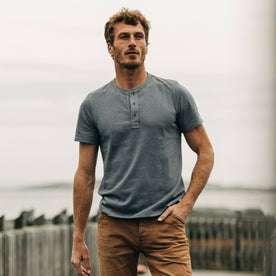 fit model wearing The Short Sleeve Heavy Bag Henley in Atlantic Blue, hand in pocket near ocean