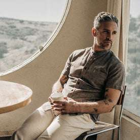 our fit model wearing The Short Sleeve Bandit in Tobacco Hemp, sitting back drinking coffee