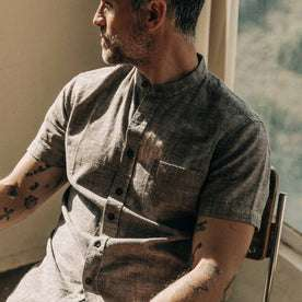 our fit model wearing The Short Sleeve Bandit in Tobacco Hemp, sitting back looking right