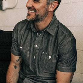our fit model wearing The Short Sleeve Popover in Charcoal Chambray—sitting in the garage, cropped shot smiling