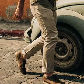 fit model wearing The Democratic All Day Pant in Aluminum Bedford Cord, cuffed next to car