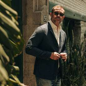 fit model wearing The Emerson Jacket in Navy Double Cloth, looking left of camera, plant on left