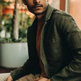 fit model wearing The Emerson Jacket in Olive Double Cloth, looking right of camera sitting down