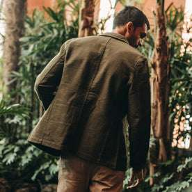 fit model wearing The Emerson Jacket in Olive Double Cloth, back shot near plants