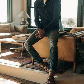 fit model wearing The Slim Jean in Organic Selvage 12-month Wash, sitting against couch
