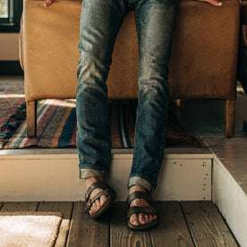 fit model wearing The Slim Jean in Organic Selvage 12-month Wash, cuffed with birks