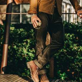 our fit model wearing The Camp Pant in Olive Corduroy—drinking a glass of whiskey