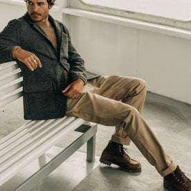 our fit model wearing The Camp Pant in Khaki Reverse Sateen—sitting on a bench