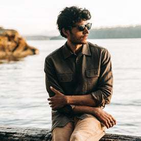 our fit model wearing The Corso in Walnut Double Cloth—sitting on log near beach