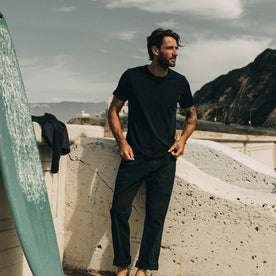 our fit model wearing The Merino Tee— on the beach, in our black colorway
