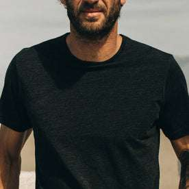 our fit model wearing The Merino Tee—in our black tee looking straight on, cropped shot
