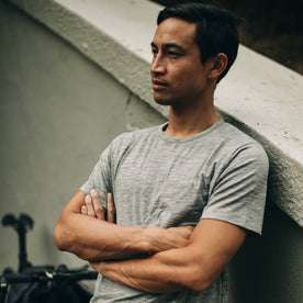 our fit model wearing The Merino Tee—in our grey shirt, arms crossed