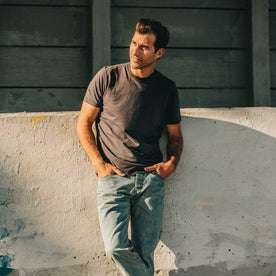 our fit model wearing The Standard Issue Tee in Charcoal Hemp—leaning against wall