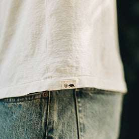 our fit model wearing The Standard Issue Tee in Natural Hemp—logo detail shot