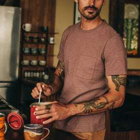 fit model wearing The Heavy Bag Tee in Burgundy, making coffee, cropped