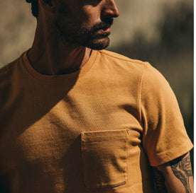 fit model wearing The Heavy Bag Tee in Saffron, looking right