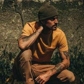 fit model wearing The Heavy Bag Tee in Saffron, kneeling, looking right