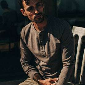 fit model wearing The Heavy Bag Henley in Espresso, sitting, playing with sleeve